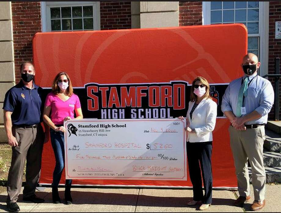 Stamford athletic director Chris Passamano (left) and principal Raymond Manka (right) present a check to Robin Druckman of Stamford Health and Gayle Alswanger, the director of development at the Bennett Cancer Center. Photo: Contributed /