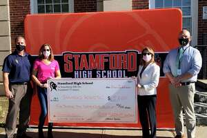 Stamford athletic director Chris Passamano (left) and principal Raymond Manka (right) present a check to Robin Druckman of Stamford Health and Gayle Alswanger, the director of development at the Bennett Cancer Center.