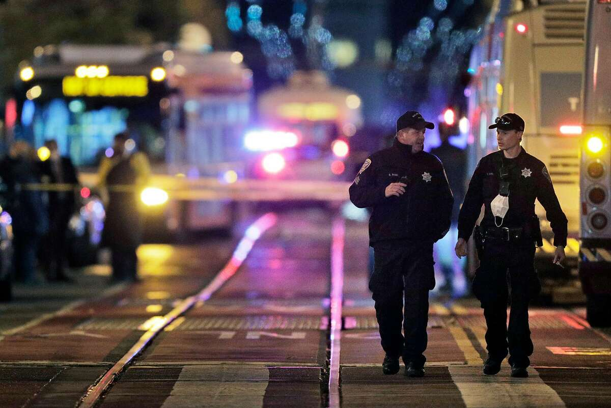 Investigators look over the scene of a police shooting on Market Street outside the Powell Street Bart Station and Westfield Shopping Center in San Francisco, Calif., on Tuesday, November 17, 2020.