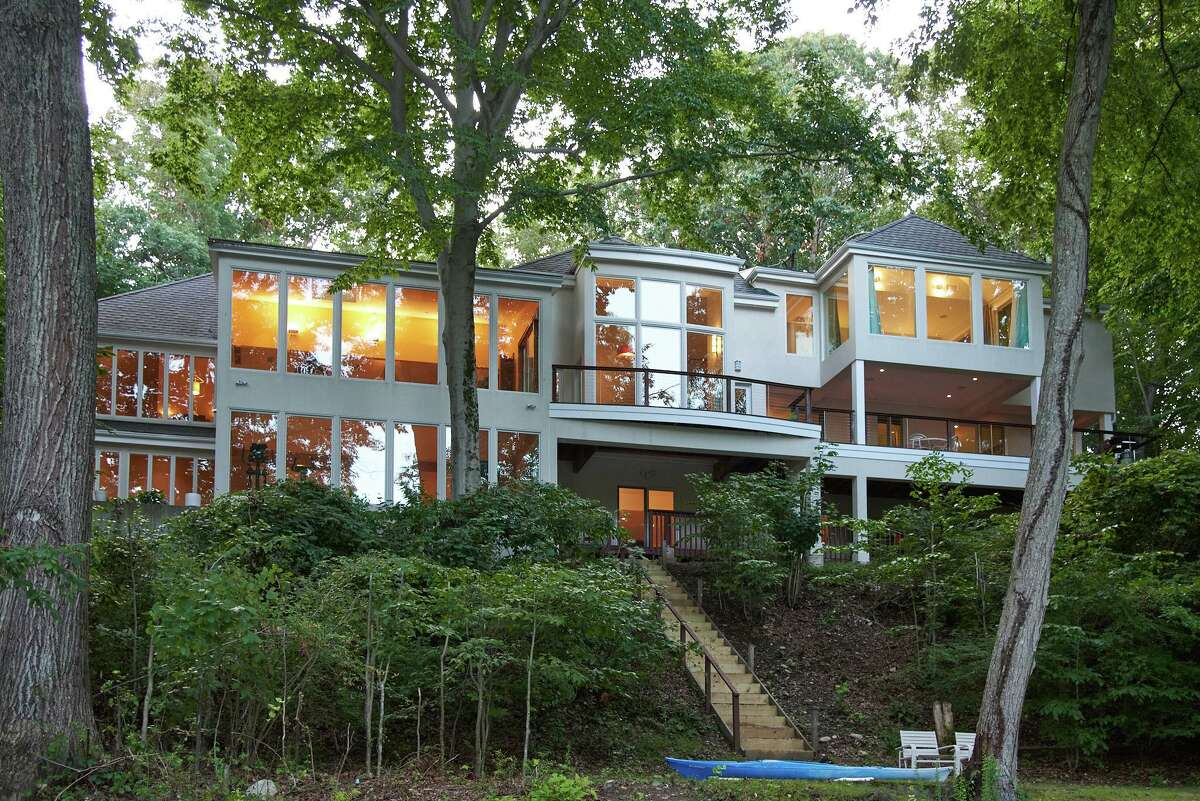 The European-style contemporary house at 10 River Lane in Westport features large two-story windows and two large decks to enjoy views of the Saugatuck River. The original house that stood on this 1.54-acre level and sloping waterfront property in the Old Hill neighborhood was torn down. This one was custom built in its place, taking full advantage of the scenic setting along the Saugatuck River. They gave the off-white stone and stucco house exquisite architectural details and design elements, green features to earn an Energy Star rating, 6,376 square feet of living and entertaining space, and disability access including 32-inch minimum door widths, 60-inch turning radius and hallways at least 36 inches wide. There are also extraordinarily tall ceilings and an abundance of two-story glass walls that allow for views of the river from every room. Those walls of glass give its residents the impression that they are living in a treehouse, a rather elegant and sophisticated treehouse.