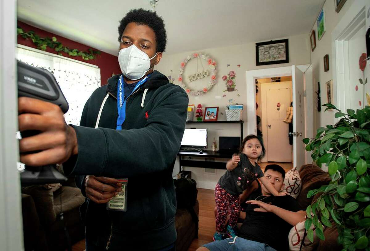 Using an X-ray fluorescence (XRF) instrument, Bridgeport lead inspector Charles Tate prepares to scan an interior doorway of the multifamily Wood Avenue house. Looking on are Rocio Valladares, 2; and her brother Angel Valladares, 14.