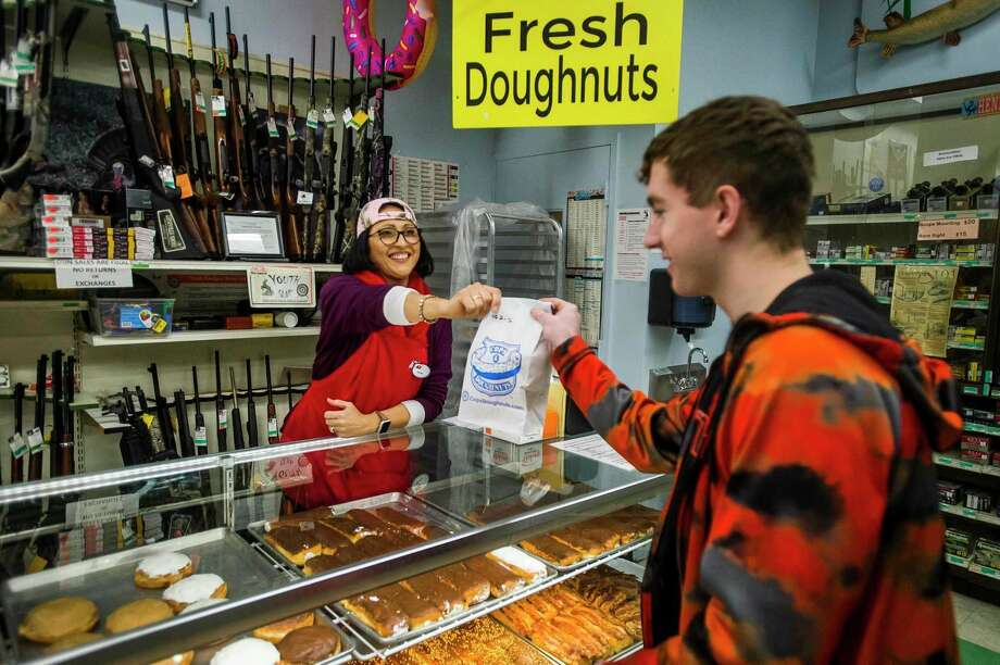 Belinda Kuchek hands a bag of doughnuts to Jake Grames before he makes his purchase Monday morning at Ace Hardware & Sports in Midland. The store now sells doughnuts from Cops & Doughnuts, a popular Clare city bakery. (Katy Kildee/kkildee@mdn.net)