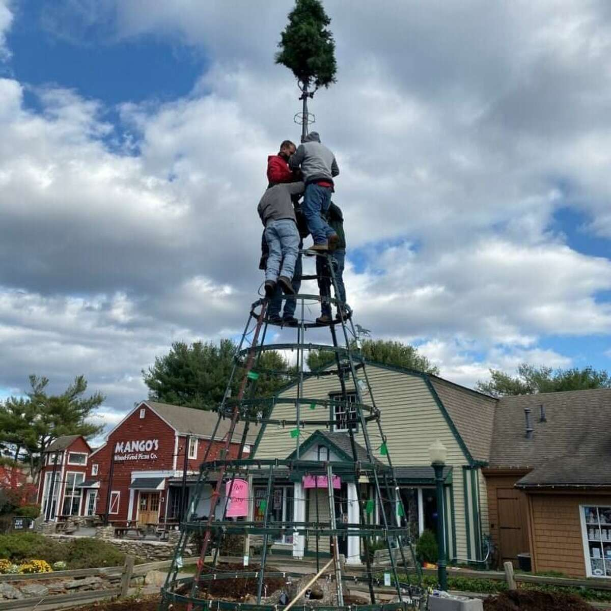 Workers set up a central element of the new light display at Olde Mistick Village recently. The shops will be open from 10 a.m.-8 p.m. Monday through Thursday, 10-9 on Fridays and Saturdays and 11-6 on Sundays.