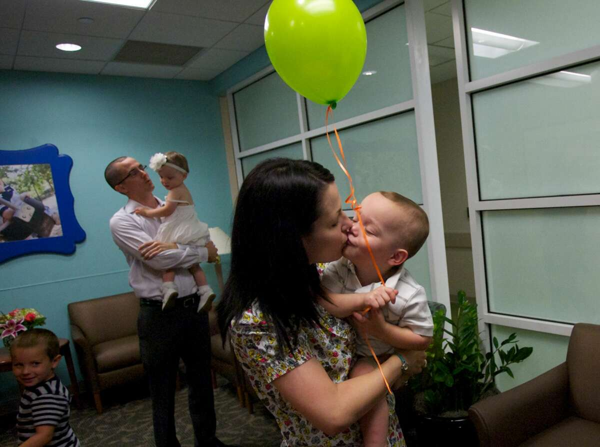 """Portrait photographer Brittani Oliver kisses her son Cullen during the unveiling of Memorial Hermann Hospital's newly renovated NICU as well as the debut of """"The Walls of Hope"""" project featuring photographs taken of premature babies by Oliver."""