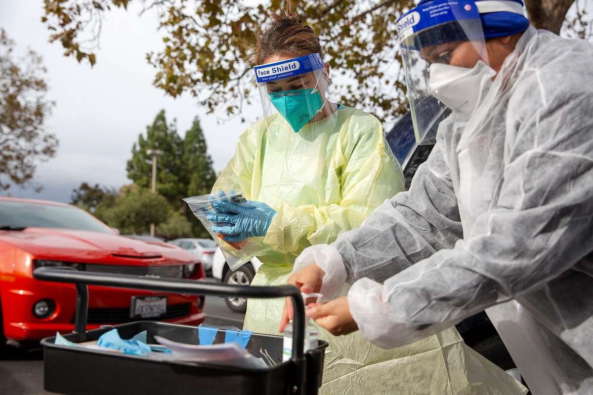Veronica V. (right) a registered Public Health nurse, and Rina Silva, a licensed vocational nurse, prepare to test a family during the Testing for Turkey Media Conference and testing at a Covid-19 testing site in Concord, Calif. on Tuesday, Nov. 17, 2020.