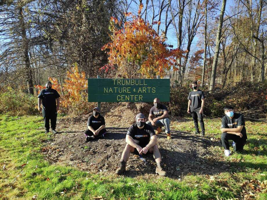 Recently, employees of the Amazon Trumbull Distribution Center volunteered at the Trumbull Nature & Arts Center (TNAC), located across the street from their facility at 7115 Main St. The group raked and blew leaves from under the large maple tree in front of the TNAC building and cut down the sunflowers for the season to help prepare the grounds for the winter season. Photo: Contributed Photos