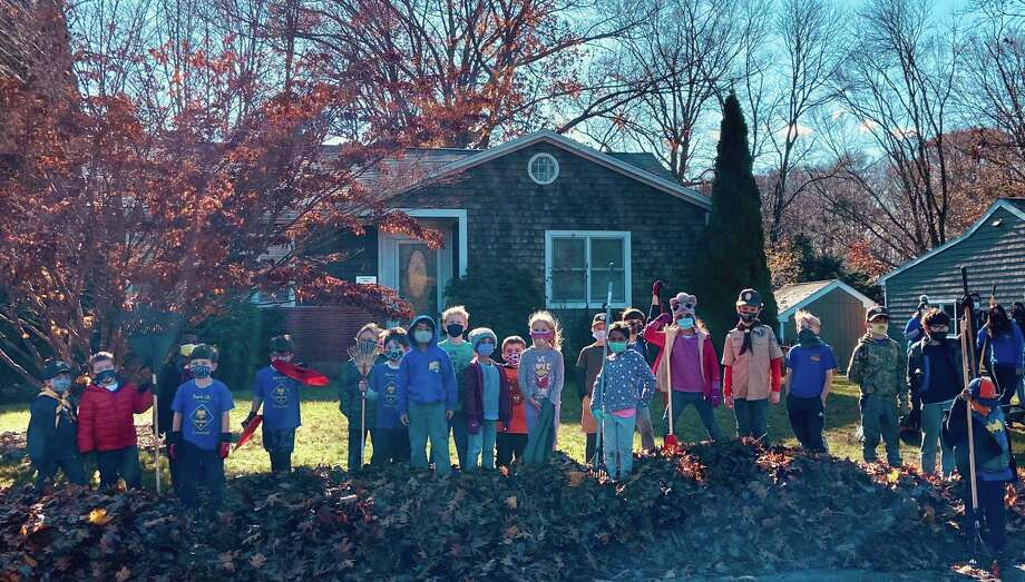 For the second consecutive year Cub Scout Pack 167 partnered with the Trumbull Rotary to help a Trumbull resident in need with cleaning their property for fall. The scouts raked leaves while being outdoors with their friends. Photo: Contributed Photo /