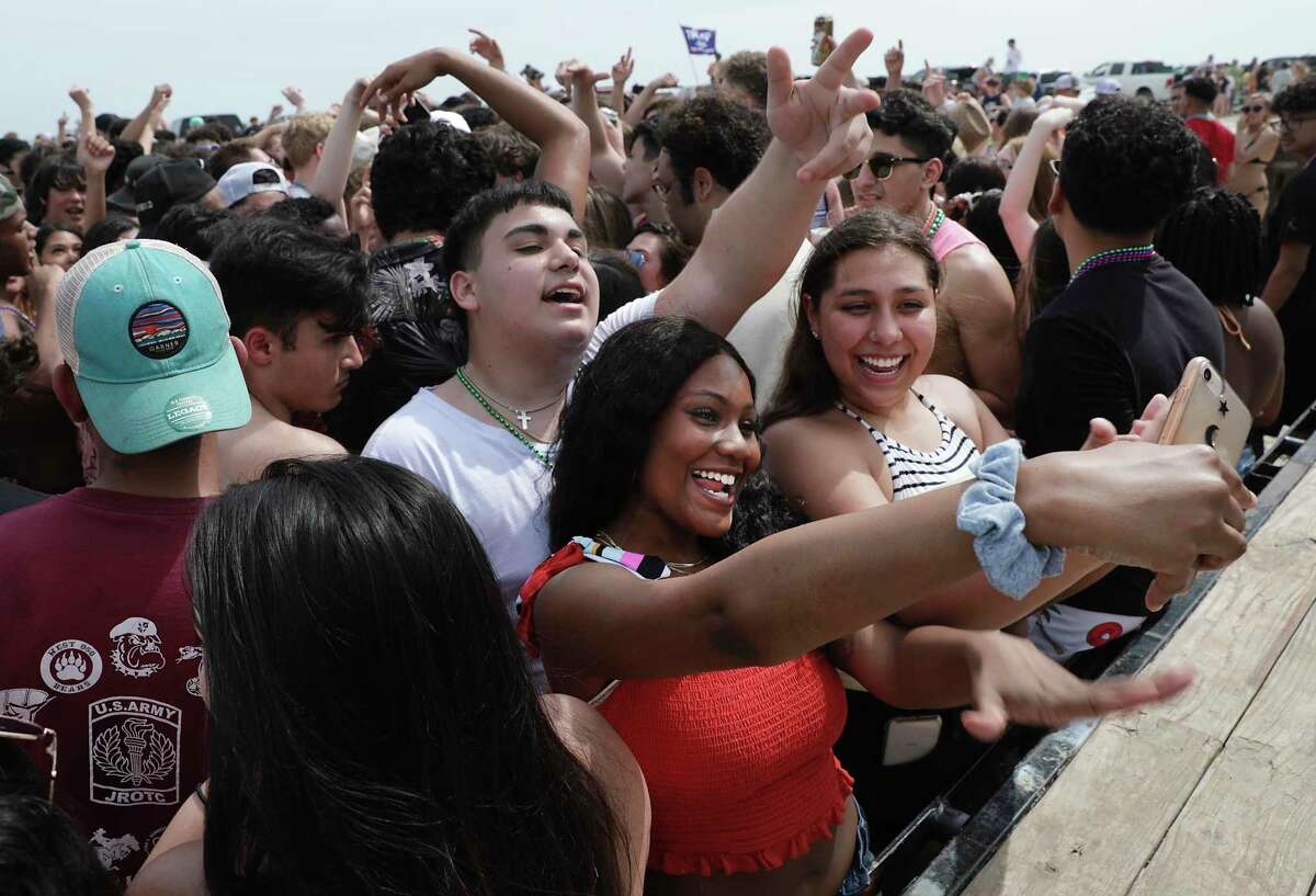 Sabrina Miller, in red, of San Antonio, takes a selfie as a large group of partiers dance to music provided by a DJ on the beach in Port Aransas on March 12. Spring Break continued unabated at beach destinations across the country even as the public began recognizing the dangers of the community spread of the coronavirus.