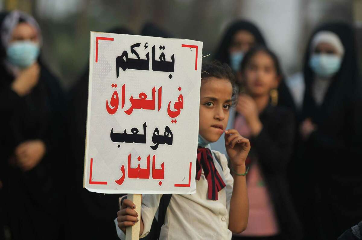A girl carries a sign reading in Arabic