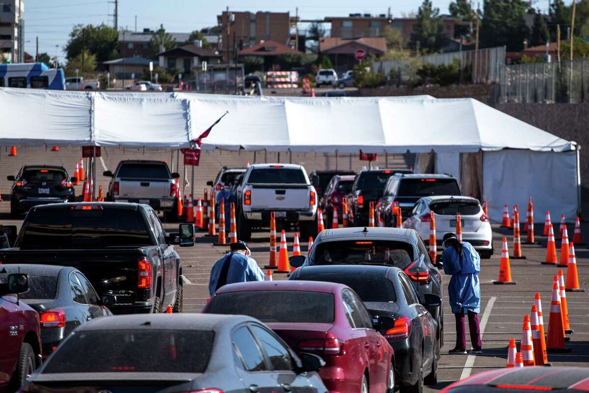 Medical workers wearing personal protective equipment (PPE) register people in vehicles at a Covid-19 drive-thru testing site in El Paso, Texas, U.S., on Monday, Nov. 9, 2020. Texas recorded more than 9,000 new cases in a 24-hour period last week, the steepest daily increase since Aug. 4, according to state health department figures.Photographer: Joel Angel Juarez/Bloomberg