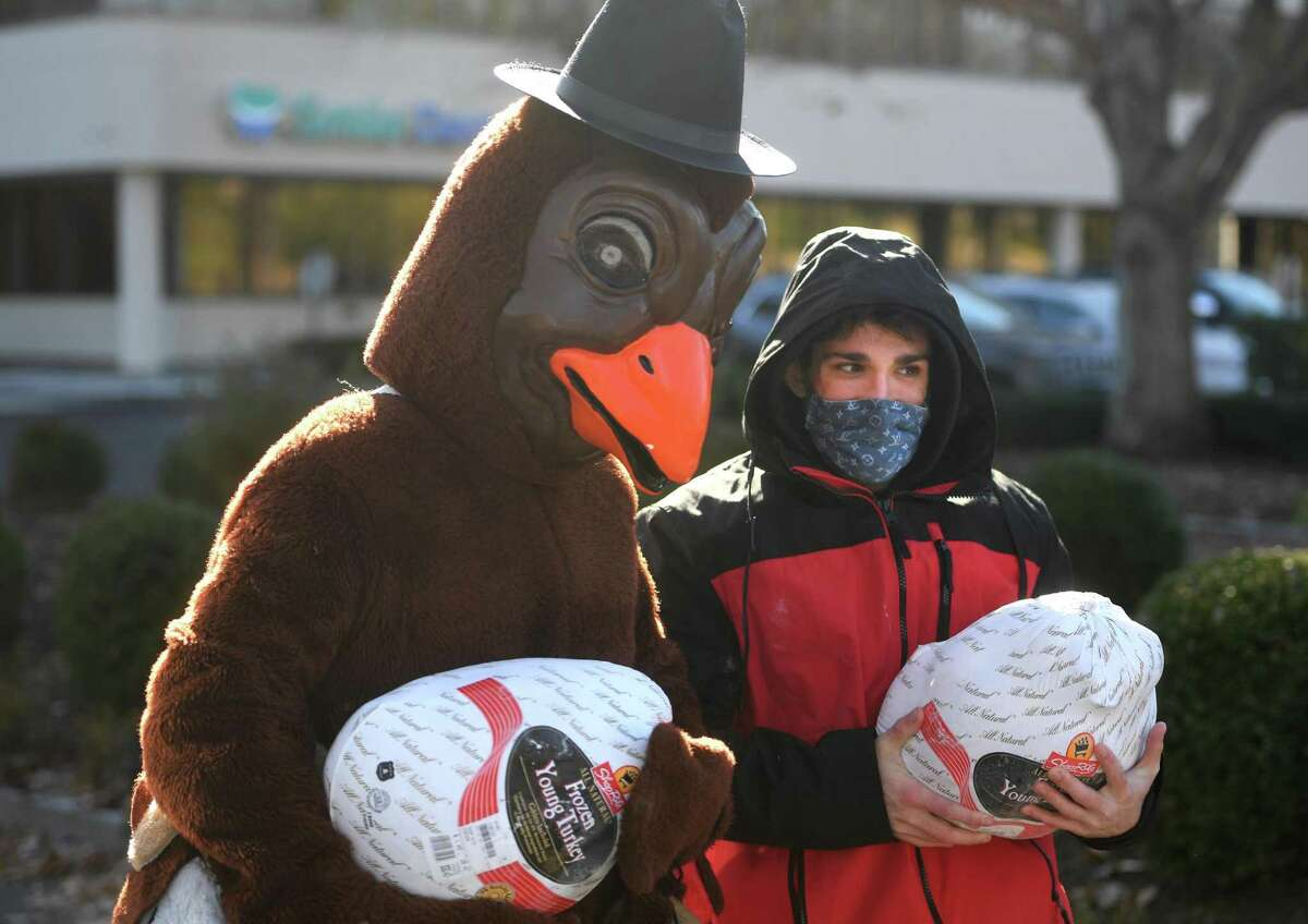 Brendan Carey, left, of Shelton, and Christian DeRosa, of North Haven, carry donated Thanksgiving turkeys during the annual food donation for the Valley Food Bank on Bridgeport Avenue in Shelton, Conn. on Wednesday, November 18, 2020.