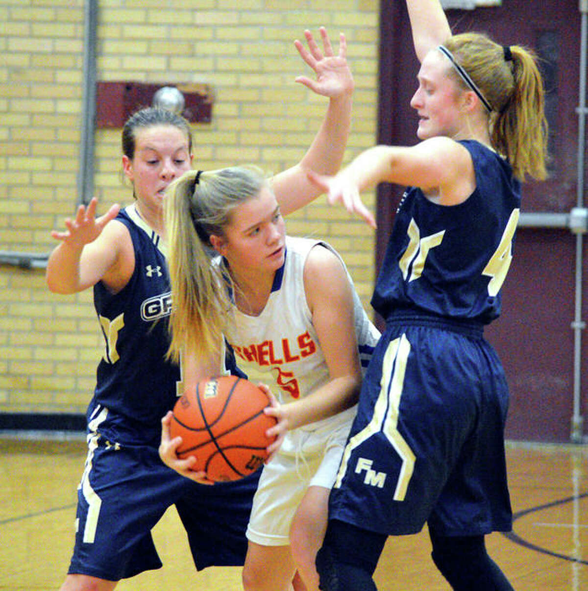Roxana's Lexi Ryan (middle) looks for a teammate while being double-teamed by Father McGivney defenders during a 2019 Dupo Cat Classic girls basketball tournament game in Dupo. The start of the prep basketball season has been 'paused' by the IHSA after the latest COVID-19 restrictions announced by Illinois Gov. JB Pritzker.