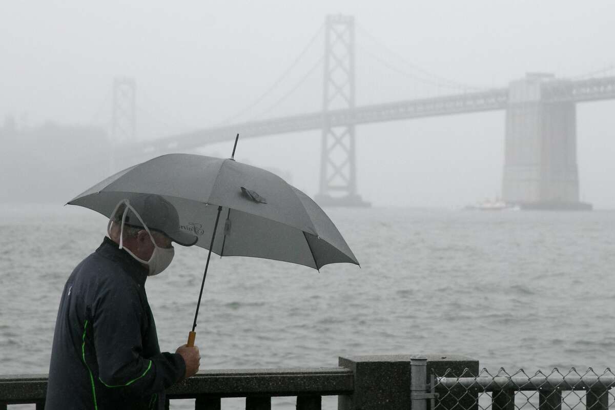 A man wearing a mask walks with an umbrella along the Embarcadero in San Francisco, California during a steady rainfall. The first significant rainstorm of the season hit the San Francisco Bay Area on Nov. 17, 2020.