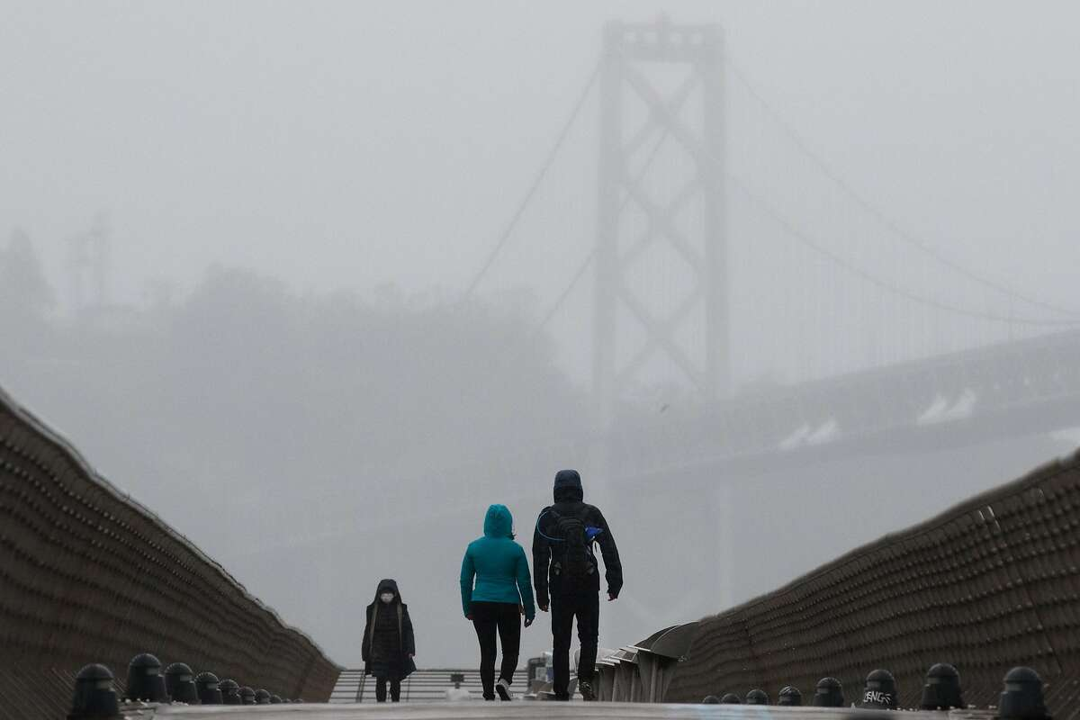 FILE PHOTO: People walk along Pier 14 with the Bay Bridge in the background in San Francisco during a steady rainfall on Nov. 17, 2020.