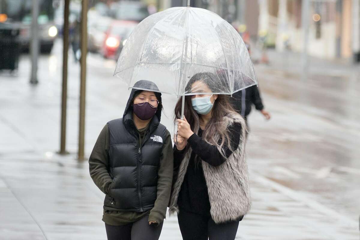 FILE - Two women wearing masks walks with an umbrella in Union Square of San Francisco, California during a steady rainfall.