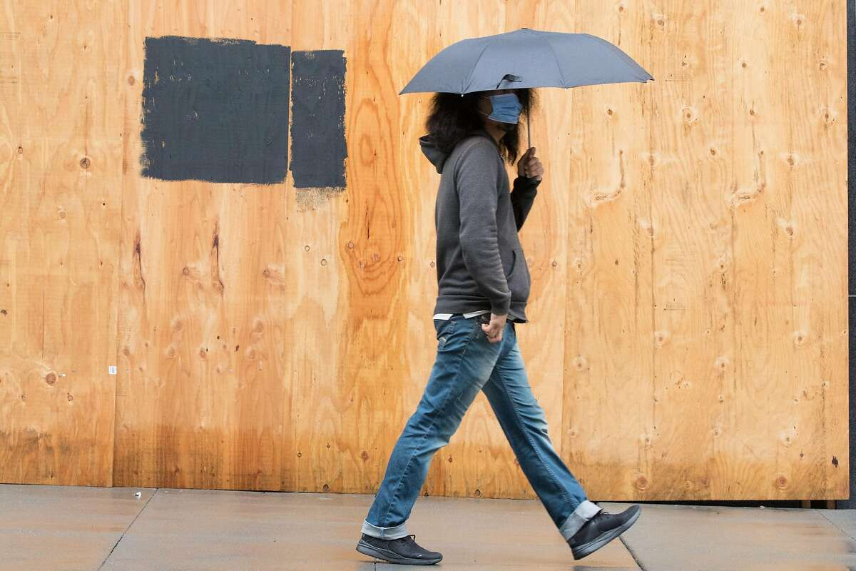 A man wearing a mask walks with an umbrella down Stockton Street in San Francisco during a steady rainfall in November. A series of storms is forecast to arrive in the Bay Area starting New Year's Day.