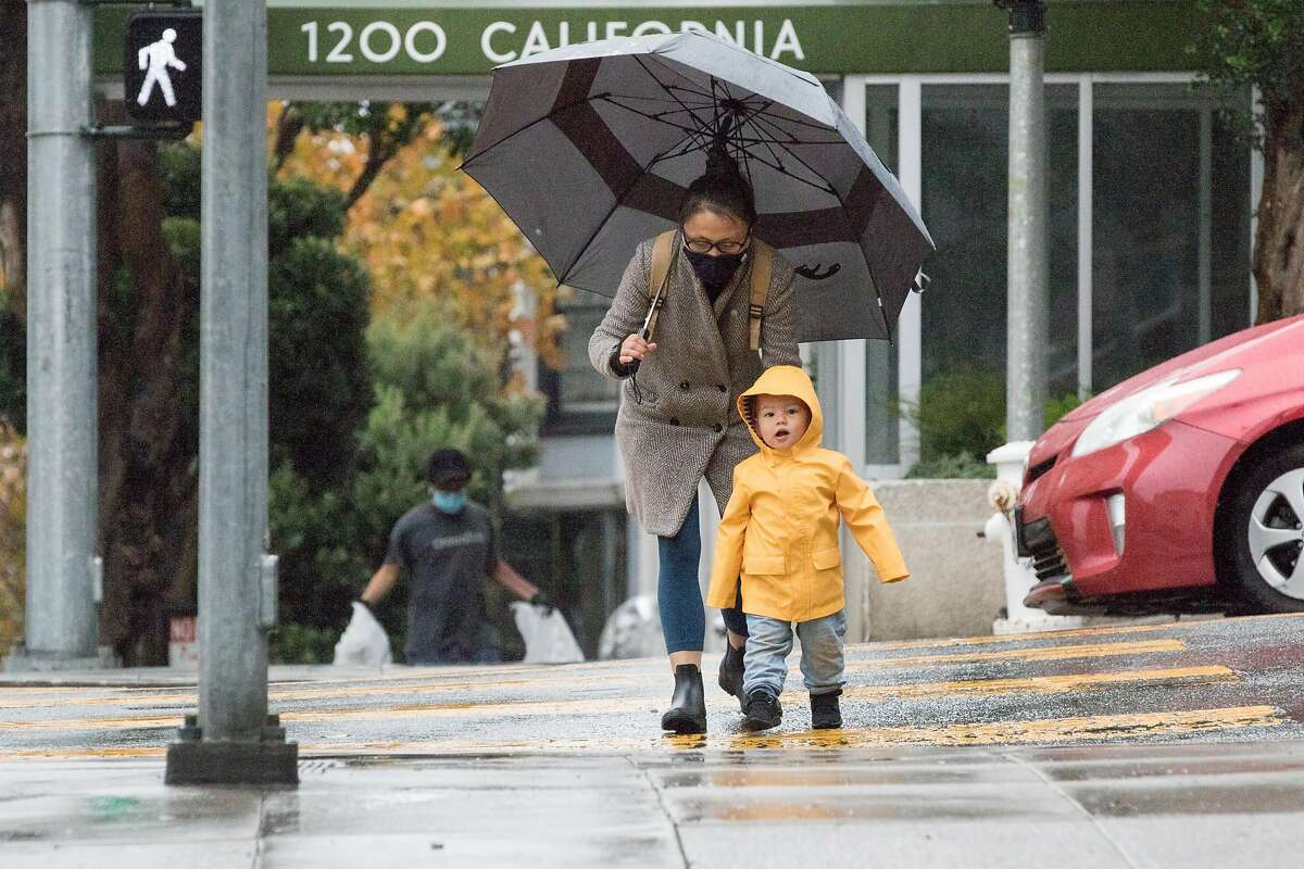 A family crosses the street in Nob Hill in San Francisco during a steady rainfall. The first significant rainstorm of the season hit the San Francisco Bay Area on Nov. 17, 2020.