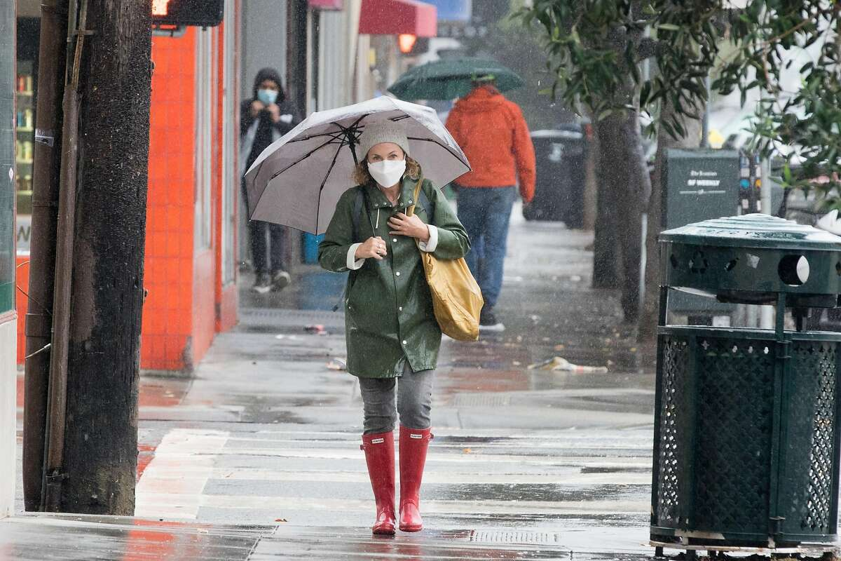 A woman wearing a mask walks with an umbrella in the Richmond District of San Francisco during a steady rainfall. The first significant rainstorm of the season hit the San Francisco Bay Area on Nov. 17, 2020.