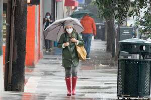 A woman wearing a mask walks with an umbrella in the Richmond District of San Francisco, California during a steady rainfall. The first significant rainstorm of the season hit the San Francisco Bay Area on Nov. 17, 2020.