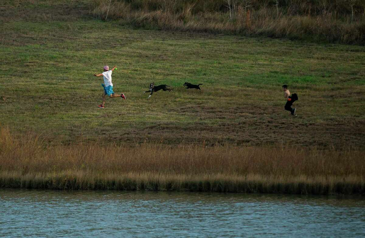 People run with their dogs at Willow Waterhole in southwest Houston on Dec. 26, 2019. The green space serves as a water retention area.