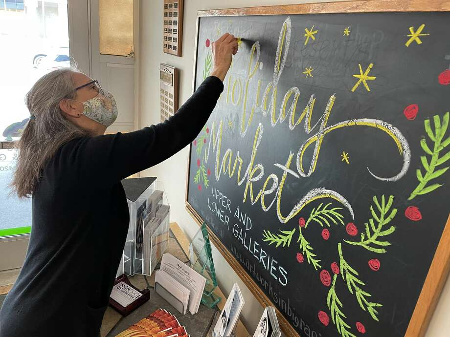 Using colorful chalk, artist Margo Berke creates a festive welcome sign near the entrance of The Painted Turtle on Wednesday in correlation to this year's Holiday Market. Berke is one of many artists to feature her talented work through the holiday season. Photo: Pioneer Photo/Bradley Massman