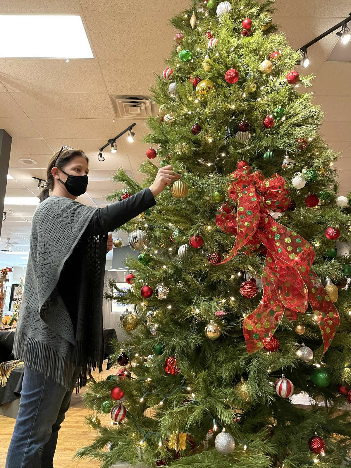 Stacie Wright, gift shop manager ofThe Painted Turtle, puts a final decoration on a Christmas tree in the Batdorff Gallery on Wednesday as this year's Holiday Marketis now underway.