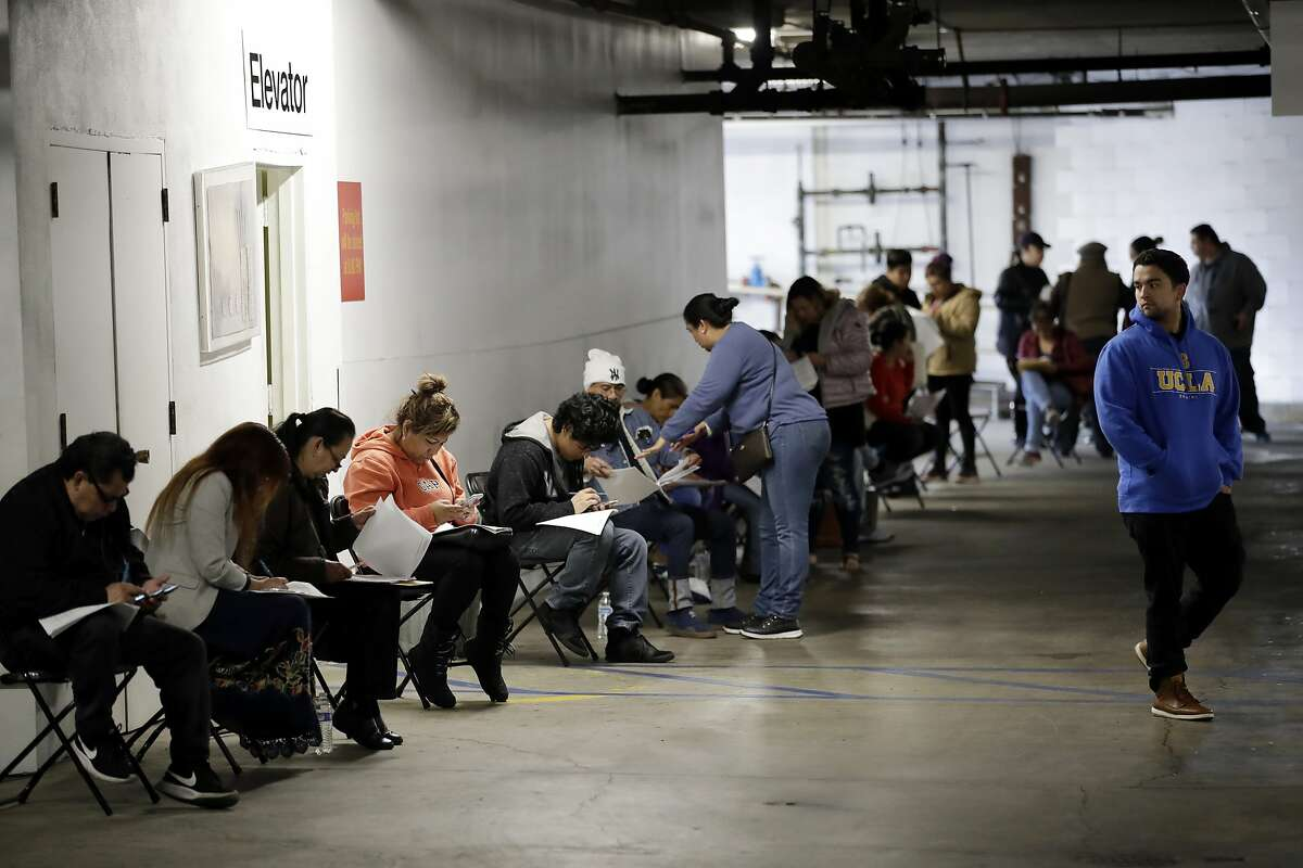 In this March 13, 2020, file photo, unionized hospitality workers wait in line in a basement garage to apply for unemployment benefits at the Hospitality Training Academy in Los Angeles. California's unemployment rate nearly tripled in April because of the economic fallout from coronavirus pandemic.