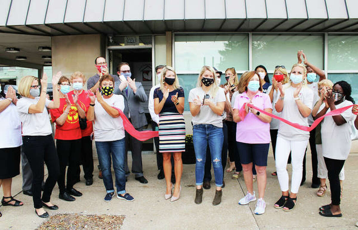Good Samaritan House board members, including Alex Madron and her mother, Angie Miller, who spearheaded the effort to re-open the women's shelter, at the ribbon cutting Aug. 31 for Good Samaritan House, 1825 Delmar Ave., Granite City, where now four women and their children are staying at the house. Residents can stay from as short as one night to three months.