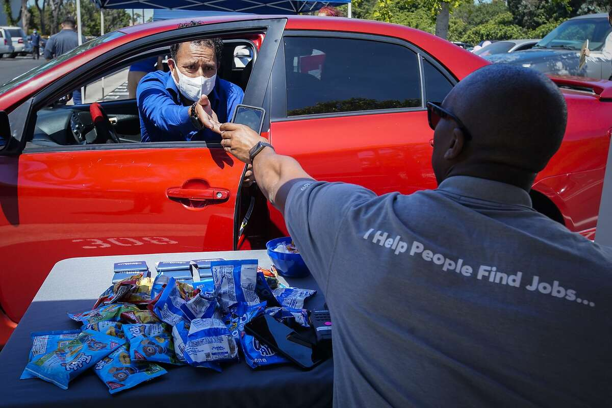 In this Wednesday, May 6, 2020, photo, Brandon Earl, right, helps David Lenus, a job seeker, fill out an application at a drive up job fair for Allied Universal during the coronavirus pandemic, in Gardena, Calif.