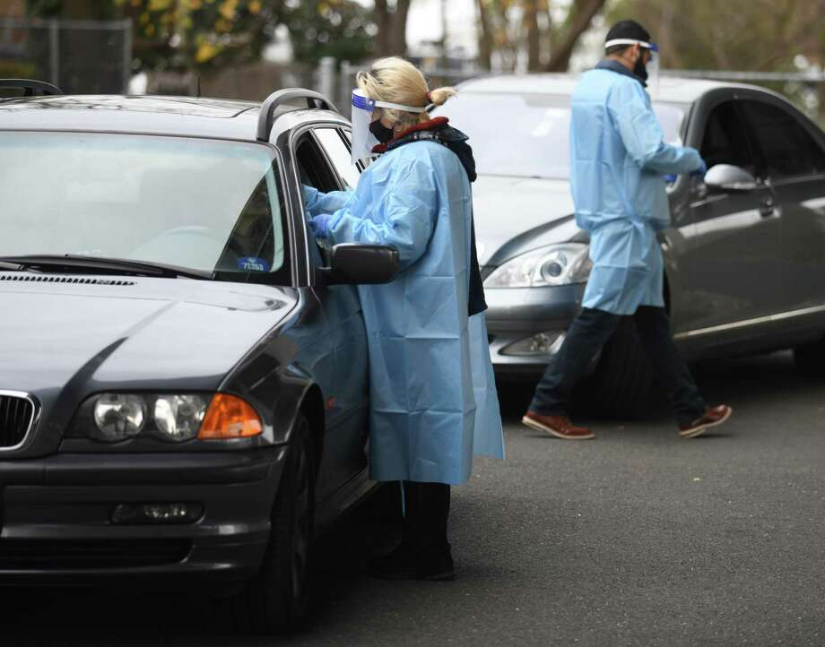 Laboratory technician Daphne Henri and office manager Javier Ortiz administer drive-thru COVID-19 tests outside The Doctors Office in the Cos Cob section of Greenwich, Conn. Tuesday, Nov. 17, 2020. The Doctors Office offers drive-thru COVID-19 nasal PCR tests during normal business hours. Photo: Tyler Sizemore / Hearst Connecticut Media / Greenwich Time