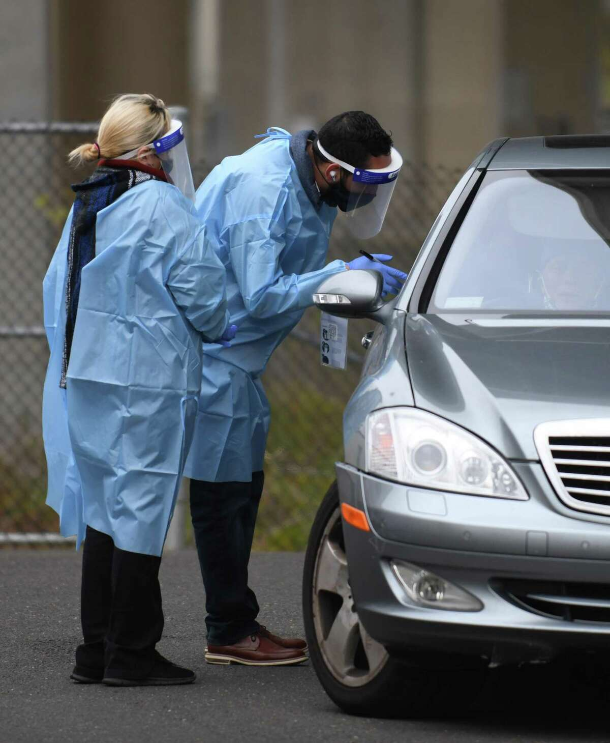 Laboratory technician Daphne Henri and office manager Javier Ortiz administer drive-thru COVID-19 tests outside The Doctors Office in the Cos Cob section of Greenwich, Conn. Tuesday, Nov. 17, 2020. The Doctors Office offers drive-thru COVID-19 nasal PCR tests during normal business hours.
