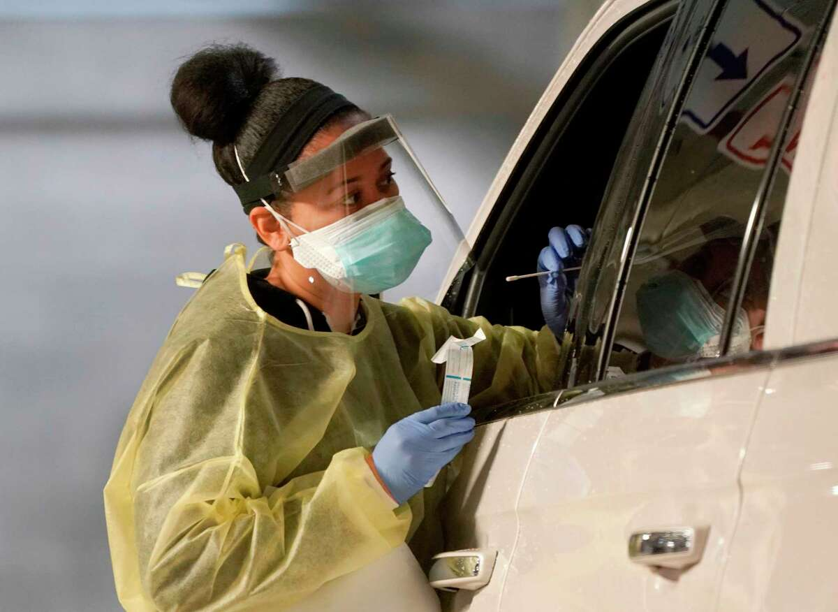 A technician gives a Covid-19 test at a drive through testing facility in Greenwich, Connecticut November 13, 2020. - Increase in cases of Covid-19 have pushed Greenwich into the