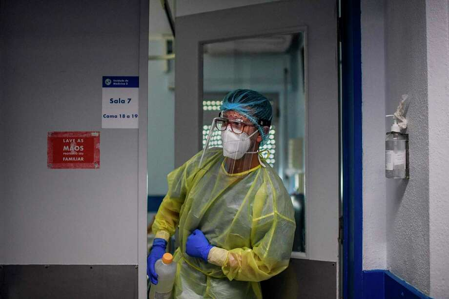 A health worker enters a room at the Covid-19 ward of the Curry Cabral hospital in Lisbon on November 18, 2020. - Pfizer and BioNTech said that a completed study of their experimental Covid-19 vaccine showed it was 95 percent effective. (Photo by PATRICIA DE MELO MOREIRA / AFP) (Photo by PATRICIA DE MELO MOREIRA/AFP via Getty Images) Photo: PATRICIA DE MELO MOREIRA / AFP Via Getty Images / AFP or licensors
