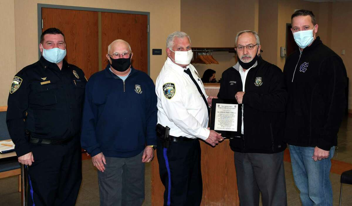 Retired Chief Russ Kniehl, second from left, and Retired Sgt. John Jarvie, second from right, present Chief Joseph Perno, center, Deputy Chief Carl Flemmig, left, and Union President Sean Faughnan, right, with the plaque.