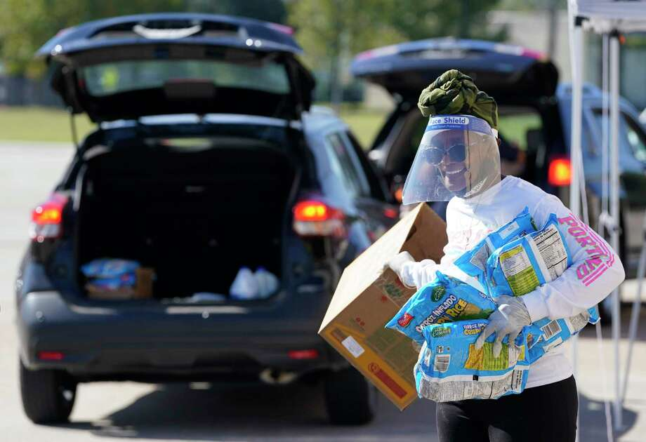 Linda Prescott carries bags of cereal to a vehicle during a food give away held at The Community of Faith, 1024 Pinemont Drive, Wednesday, Nov. 18, 2020 in Houston. The Community of Faith, Houston Black Real Estate Association, and BBVA will be hosting a food drive to collect non-perishable items on Saturday at the church from 10 am to 2 pm. Photo: Melissa Phillip, Houston Chronicle / Staff Photographer / © 2020 Houston Chronicle