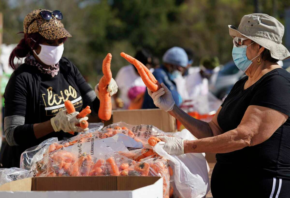 Vanessa Martin, left, and Trinidad Magana, right, sort carrots for distribution at a food give away held at The Community of Faith, 1024 Pinemont Drive, Wednesday, Nov. 18, 2020 in Houston. The Community of Faith, Houston Black Real Estate Association, and BBVA will be hosting a food drive to collect non-perishable items on Saturday at the church from 10 am to 2 pm.