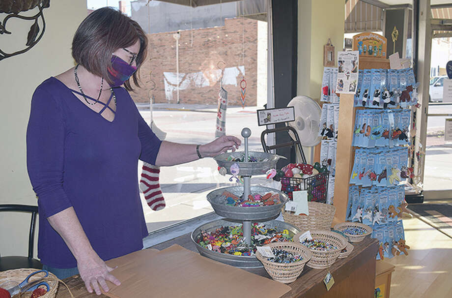 Rhonda Kircher, owner of Just Good Trade, looks through some items for sale in her store. New mitigation measures will place capacity limits on retail businesses such as Kircher's. Photo: Marco Cartolano | Journal-Courier