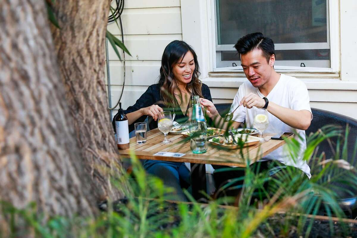 Patrons Tiffany Dang and Grantland Chew smile as they dine at Intu-On, a Thai food pop-up at a Birba wine bar.