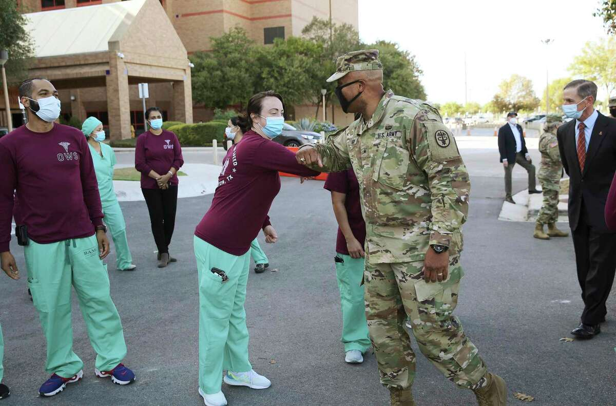 Brig. Gen. Shan K. Bagby, Brooke Army Medical Center commander, offers an elbow bump with an Operation Warp Speed staff member in announcing BAMC and Wilford Hall Ambulatory Surgical Center will be among five Defense Department facilities to conduct COVID vaccine trials under the government's Operation Warp Speed initiative.