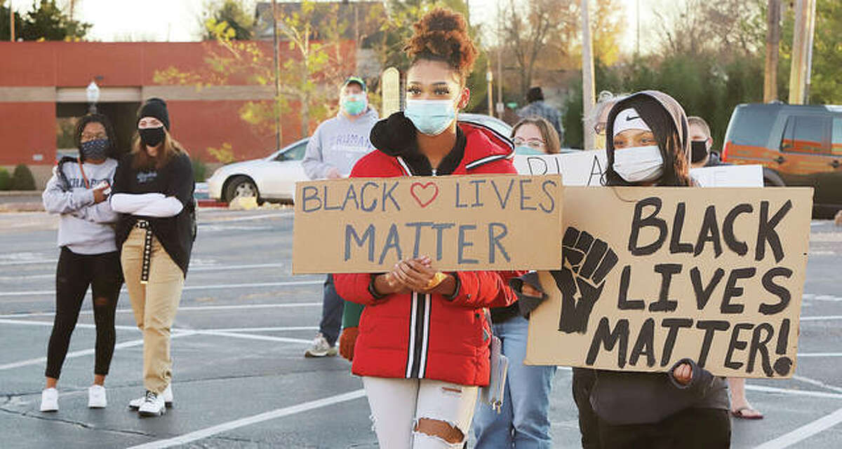 """Some of a socially distanced group of about 50 Black Lives Matter protestors hold signs on a parking lot near the Madison County Courthouse Wednesday afternoon to protest a proposed county resolution supporting police. The Madison County Board was to discuss the resolution Wednesday evening which was to support police by stating that """"Blue Lives Matter""""."""