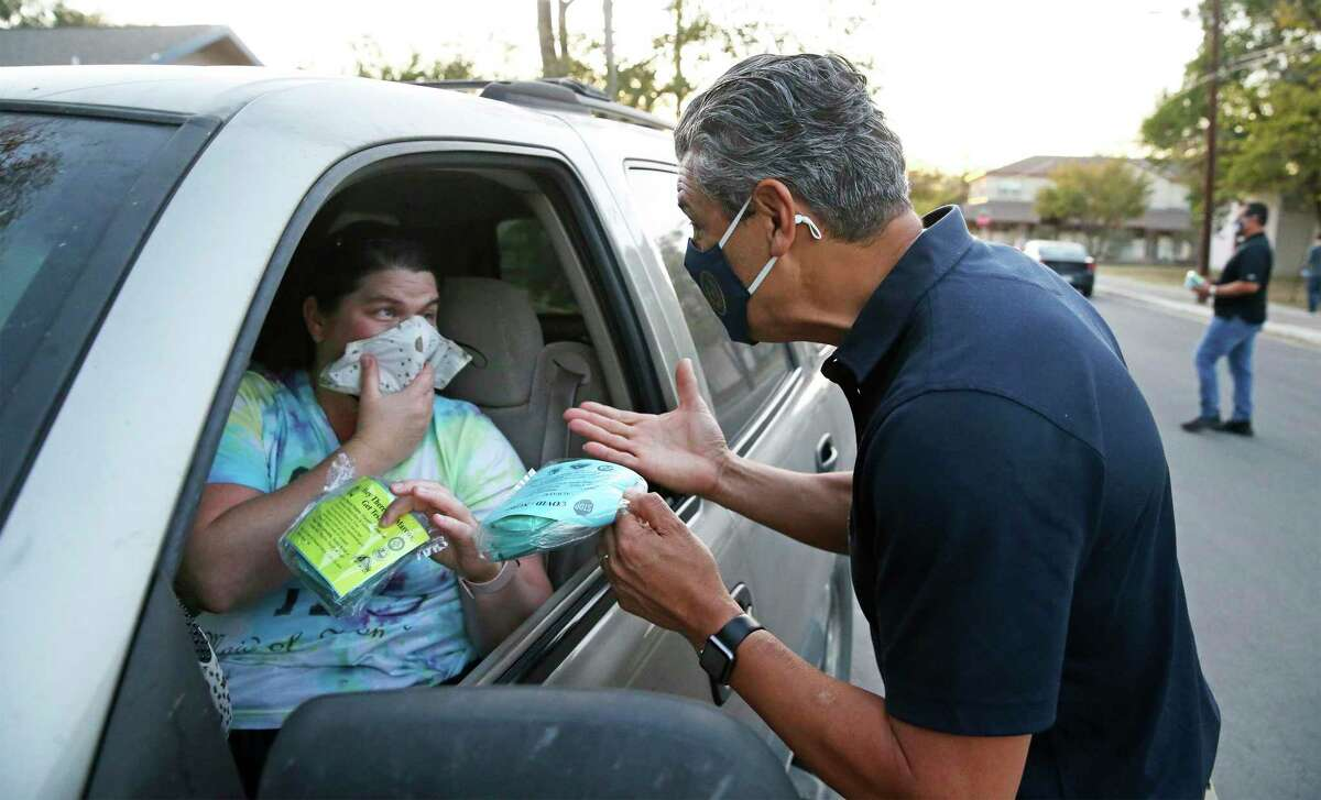 Hays County Judge Ruben Becerra, right, stresses the importance of protection as he and Emergency Management Coordinator Alex Villalobos hand out some of the 5,000 N95 masks to motorists and walk ups at the Centro Cultural Hispano de San Marcos on Nov. 18, 2020