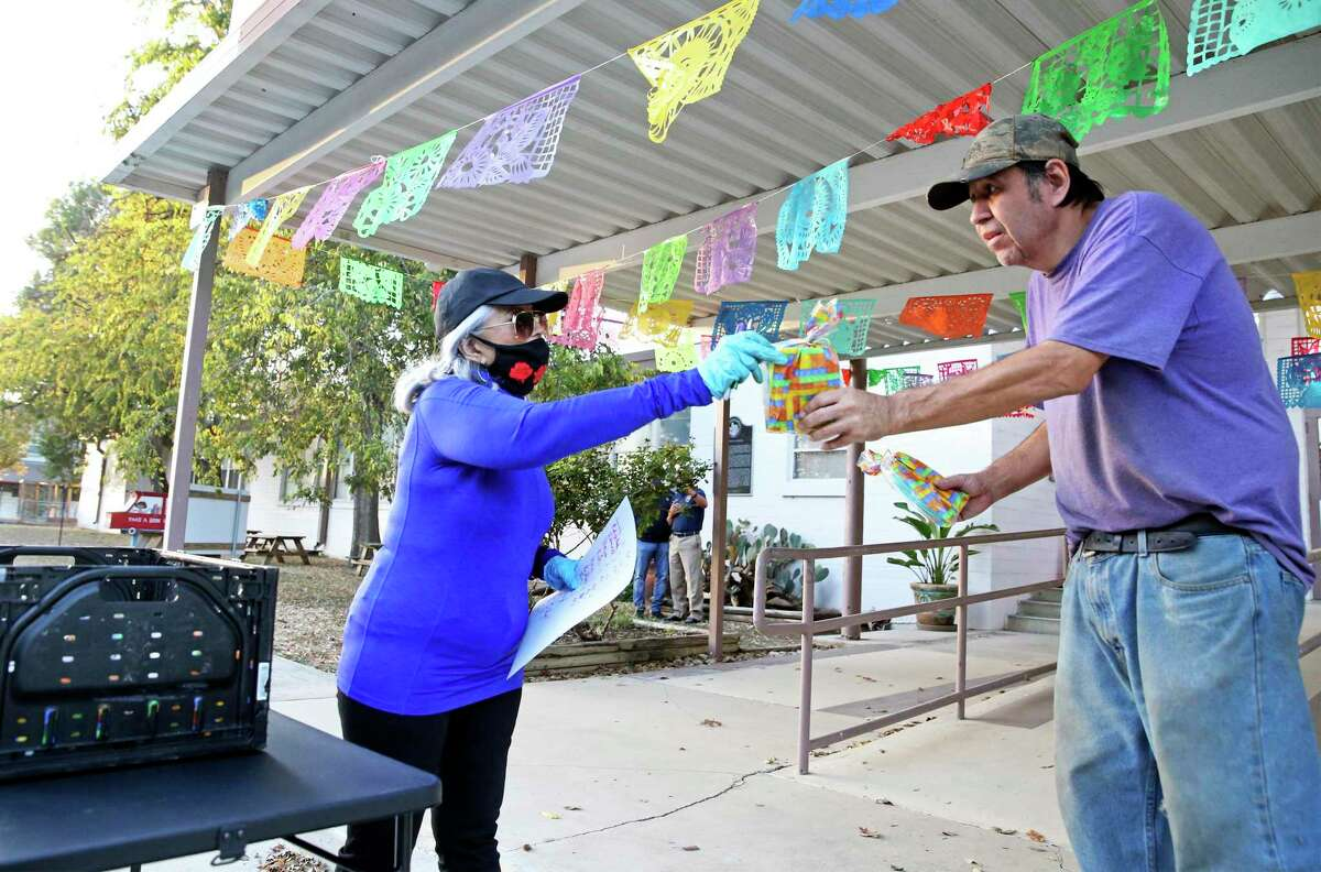 Cathi Villalpando hands out a packet of masks as Hays County Judge Ruben Becerra and Emergency Management Coordinator Alex Villalobos hand out some of the 5,000 N95 masks to motorists and walk ups at the Centro Cultural Hispano de San Marcos on Nov. 18, 2020