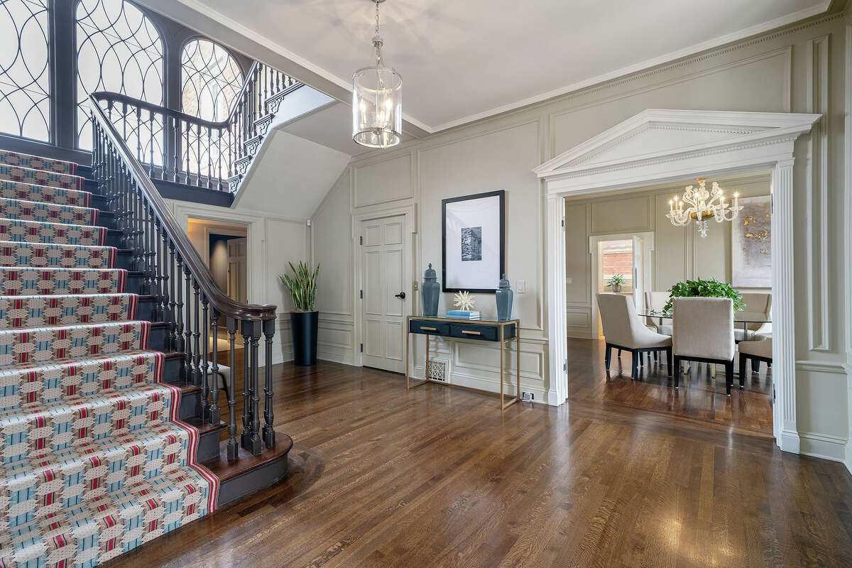 The formal entry features a grand staircase, hardwood floors, leaded windows and a formal dining room beyond the embellished doorway.