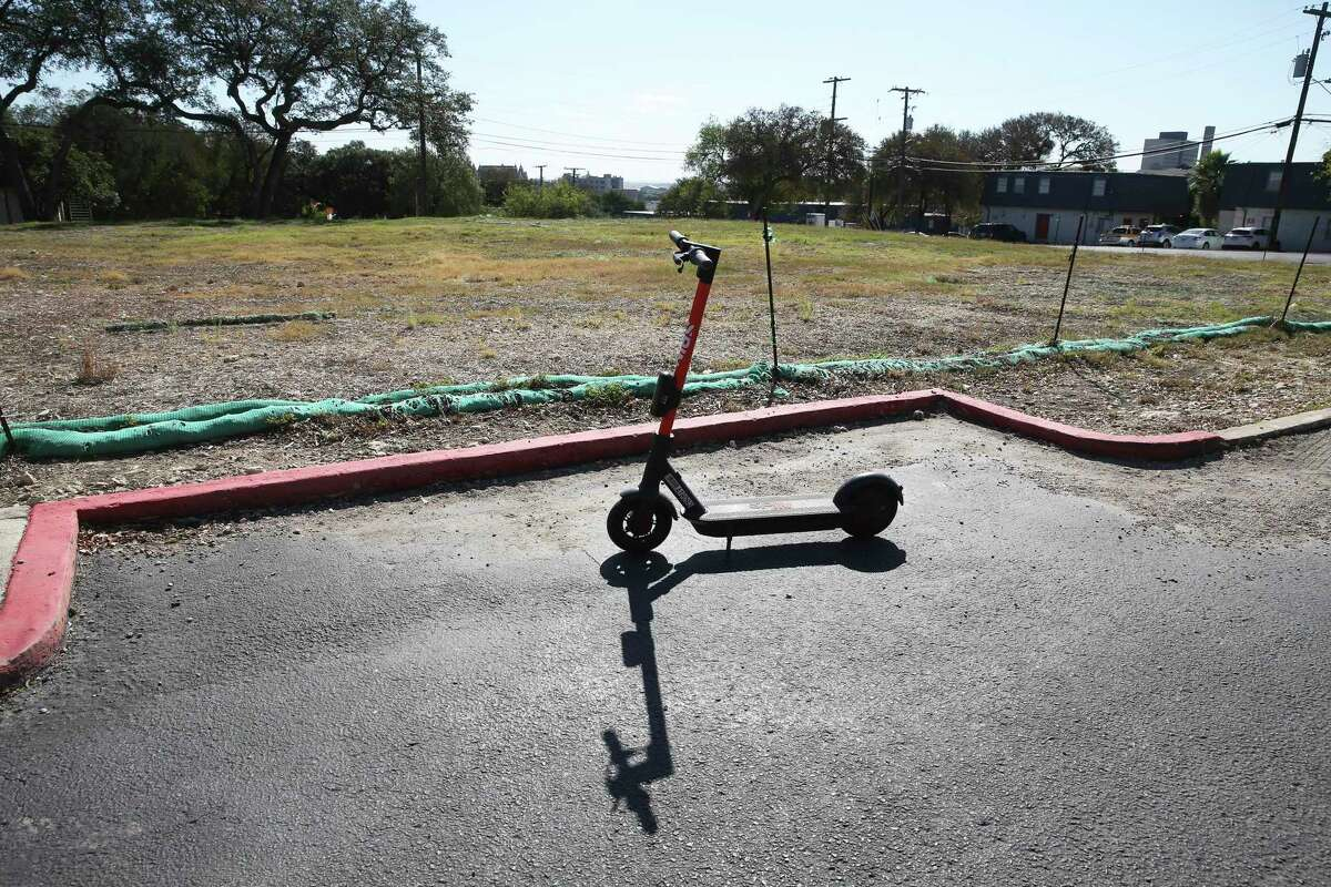A scooter stands near an empty lot where apartment buildings destroyed by fire at Iconic Village and Vintage Pads Apartments in San Marcos have since been torn down.