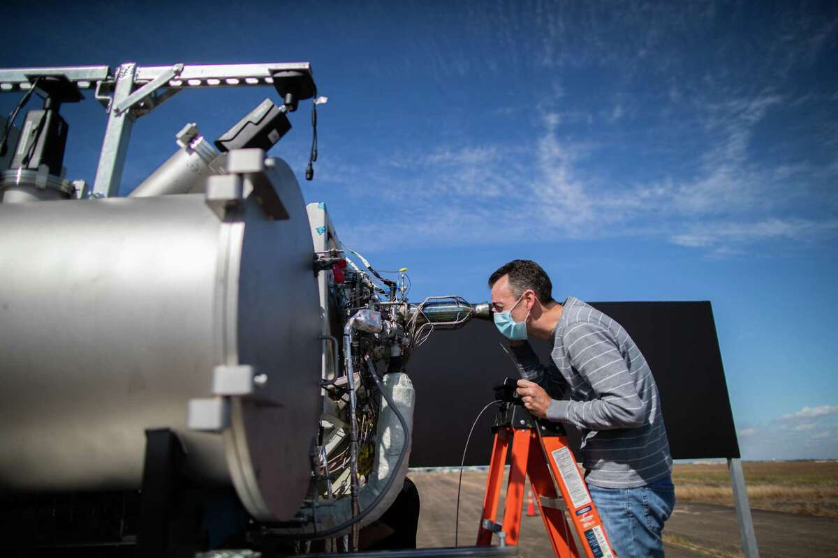 Intuitive Machines senior propulsion engineer Rob Morehead takes a look inside a rocket engine's nozzle looking for anomalies caused during the combustion of super-cold liquid oxygen and liquid methane during a test, Thursday, Nov. 5, 2020, in Houston.