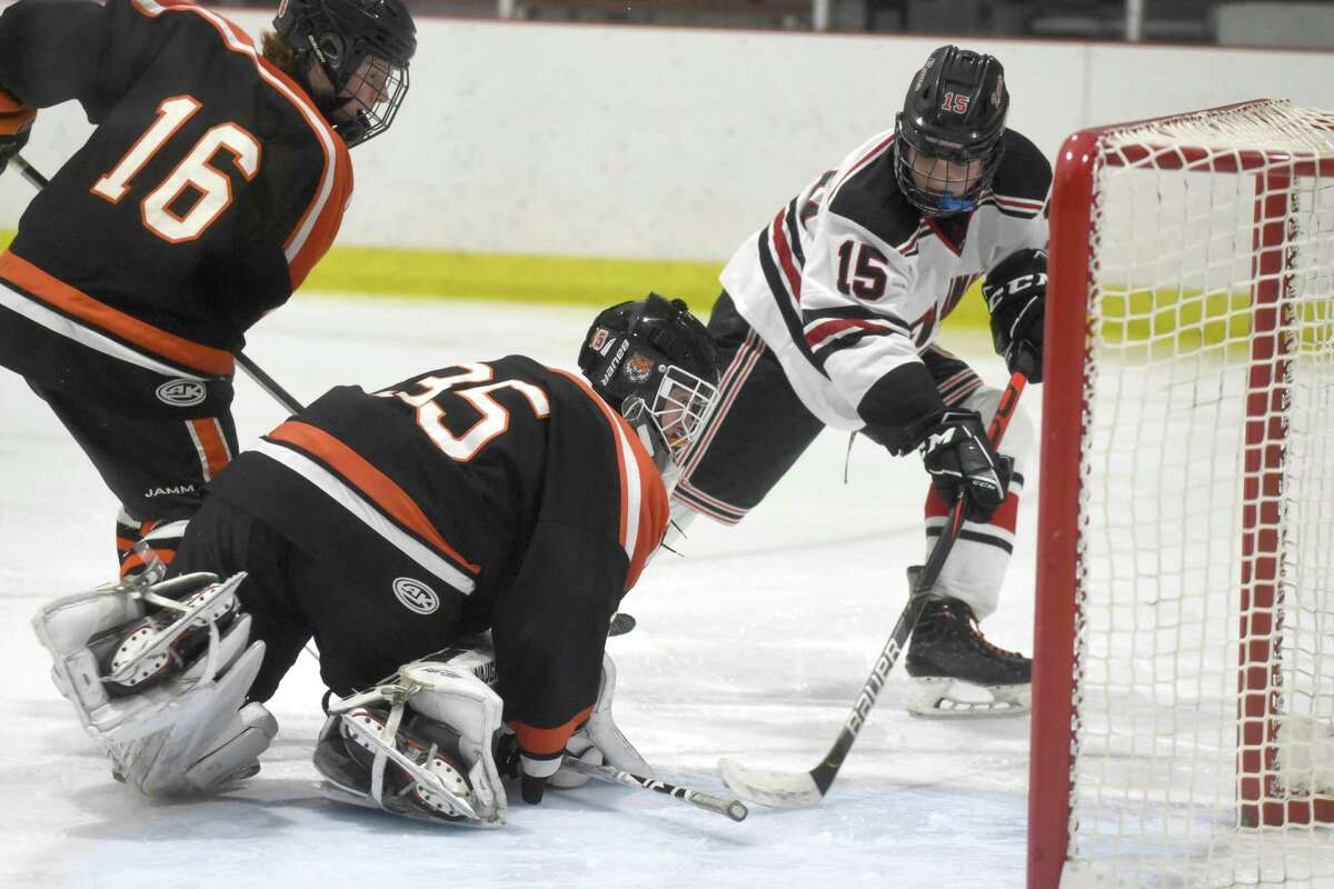 Ridgefield goalie Matthew Silliman stops the puck after a shot by New Canaan's Nick Megdanis (15) during the FCIAC boys ice hockey semifnals at the Darien Ice House on March 4.
