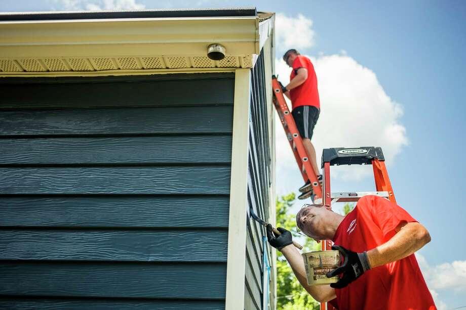 Volunteers paint siding on a homeas part of the Midland County Habitat for Humanity's Neighborhood Revitalization Initiative on Wednesday, Aug. 7, 2019. (Katy Kildee/kkildee@mdn.net)