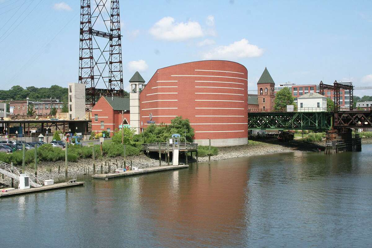 """The Maritime Aquarium, with the IMAX Theater, right, and the railroad bridge being redone to the right of that. Dave Sigworth, the Aquarium spokesman, says the portion of the venue with the IMAX theater is in fact being removed as part of a federal railroad bridge replacement project. The theater's limited reopening will run through Martin Luther King Jr. weekend with fan-favorite flicks of about 45 minutes each from the past 30 years - albeit with COVID-19 protocols in place that reduce the theater's capacity from 310 to 80. Sigworth reminds us that IMAX (which stands for Image Maximum) is the largest film format in the world. Instead of a vertically mounted projector like a 16mm, """"IMAX reels weigh about 200 pounds and the film is horizontal. ... It's a horizontal projection system. They lay flat."""""""