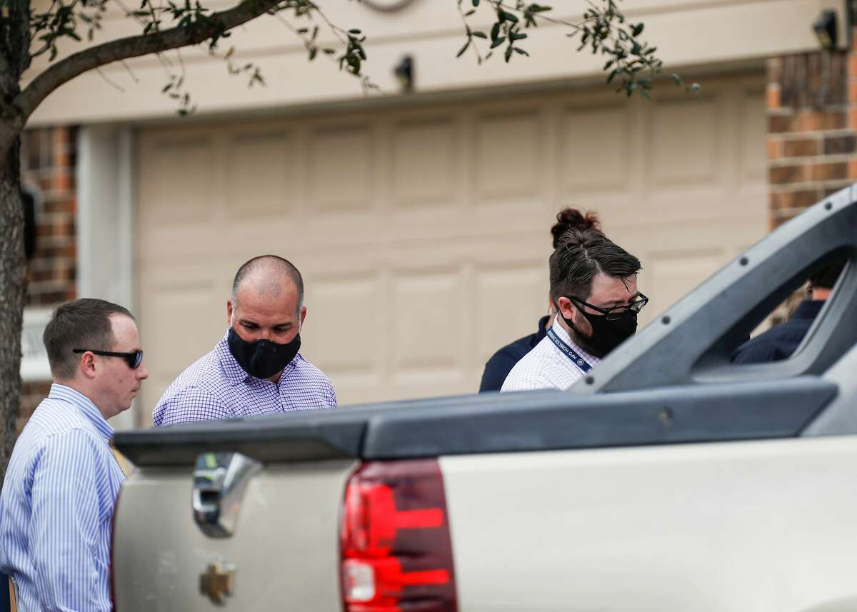 Houston Police and Fort Bend Medical examiners investigate the scene where a man was fatally shot outside his home on the 2100 block of Summit Meadow Drive on Thursday, Nov. 19, 2020, in Missouri City, Texas. Detectives believe the man was shot while trying to stop suspects from robbing his vehicle.