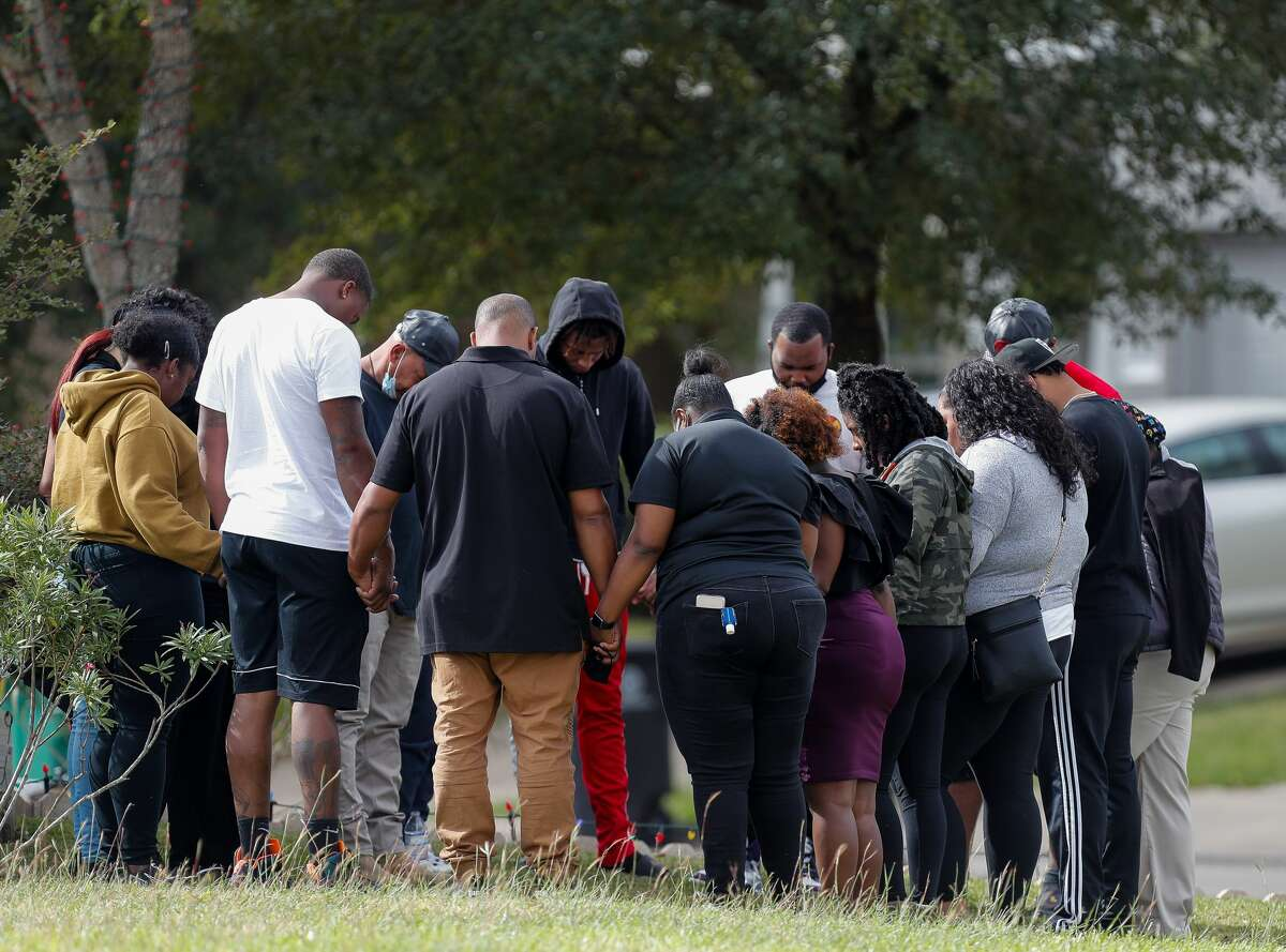 Family and friends pray in a circle as Houston Police officers and and Fort Bend Medical examiners investigate the scene where a man was fatally shot outside his home on the 2100 block of Summit Meadow Drive on Thursday, Nov. 19, 2020, in Missouri City, Texas. Detectives believe the man was shot while trying to stop his vehicle from being robbed.